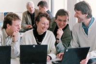 Four people in foreground looking at screen on laptop and smiling. Two people in background